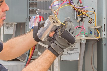 Hvac technician checking a run capacitor on a condenser